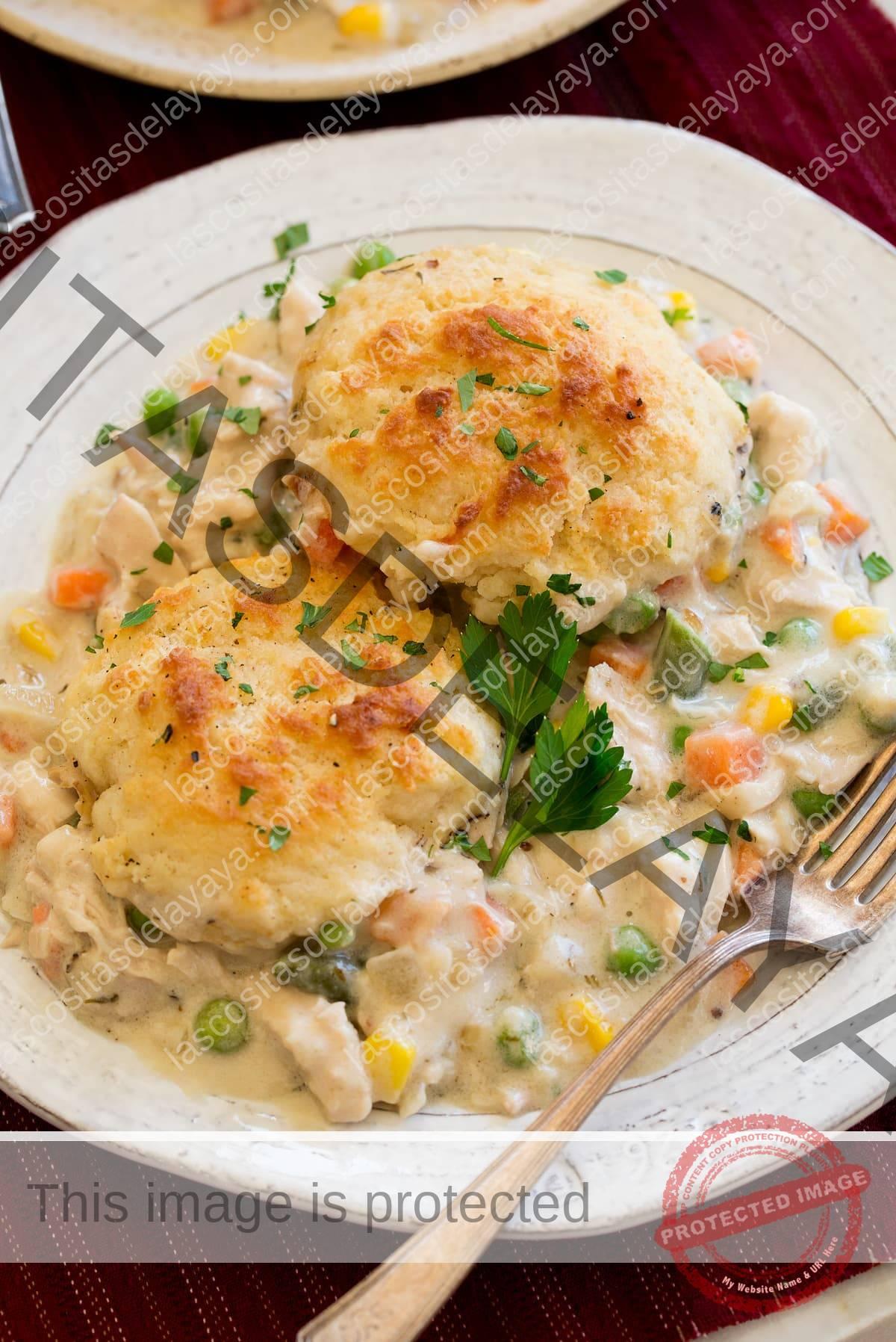 Porción de pastel de pollo y galletas en un plato blanco con un tenedor al lado.