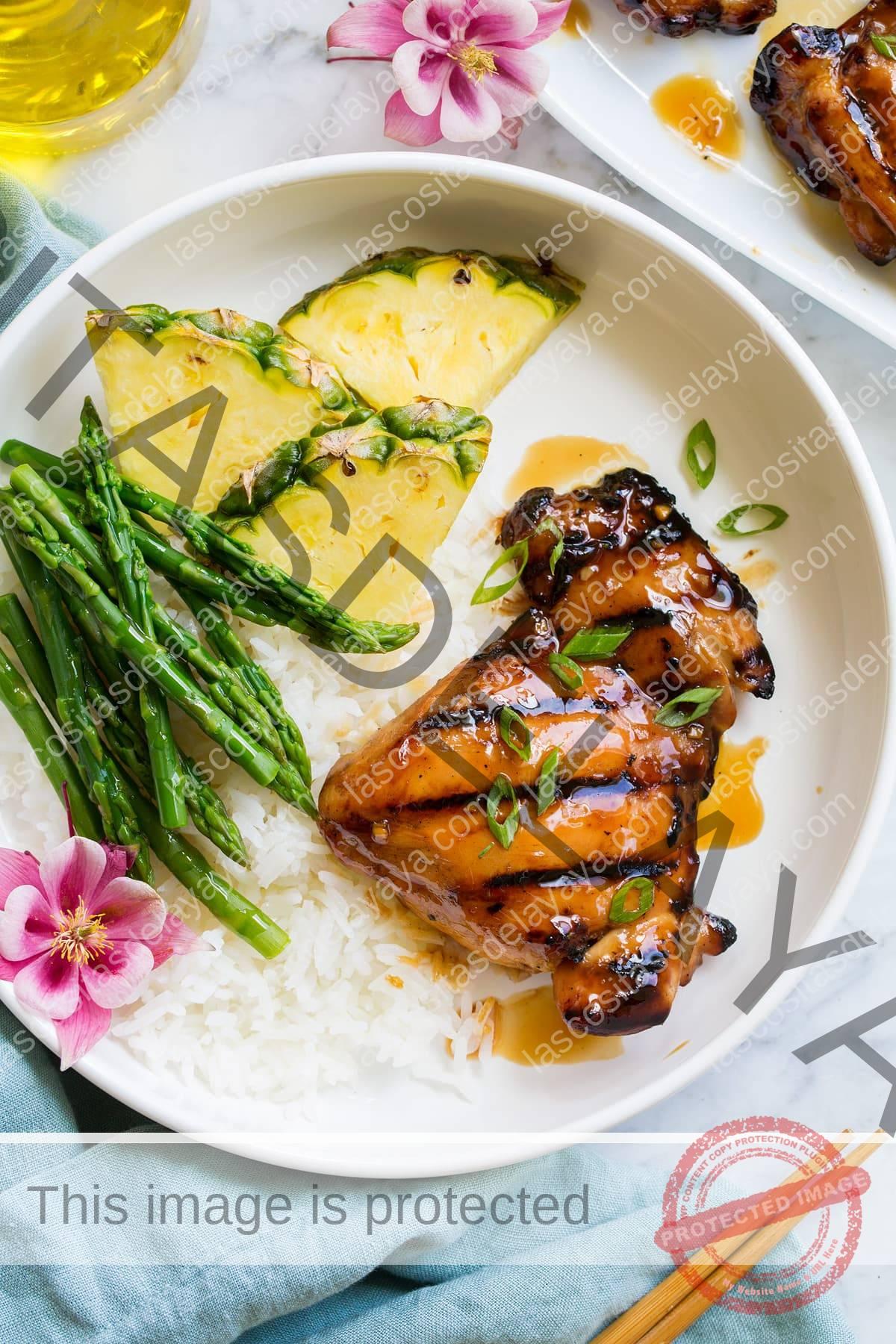 Trozo de pollo teriyaki marinado y a la plancha servido con arroz, espárragos y piña fresca.