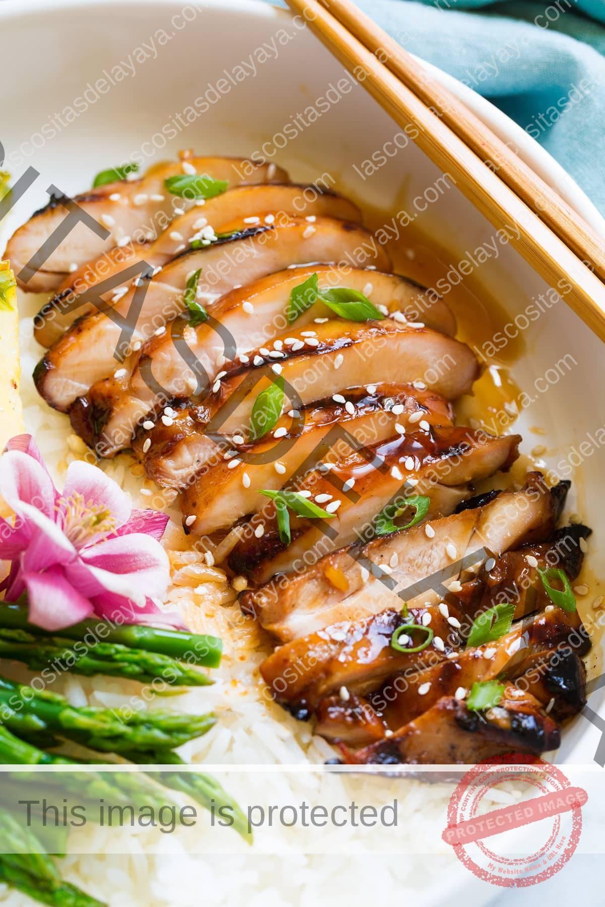 Pierna de pollo en rodajas que se muestra después de cocinar, cubierta con salsa teriyaki, semillas de sésamo y cebollino.
