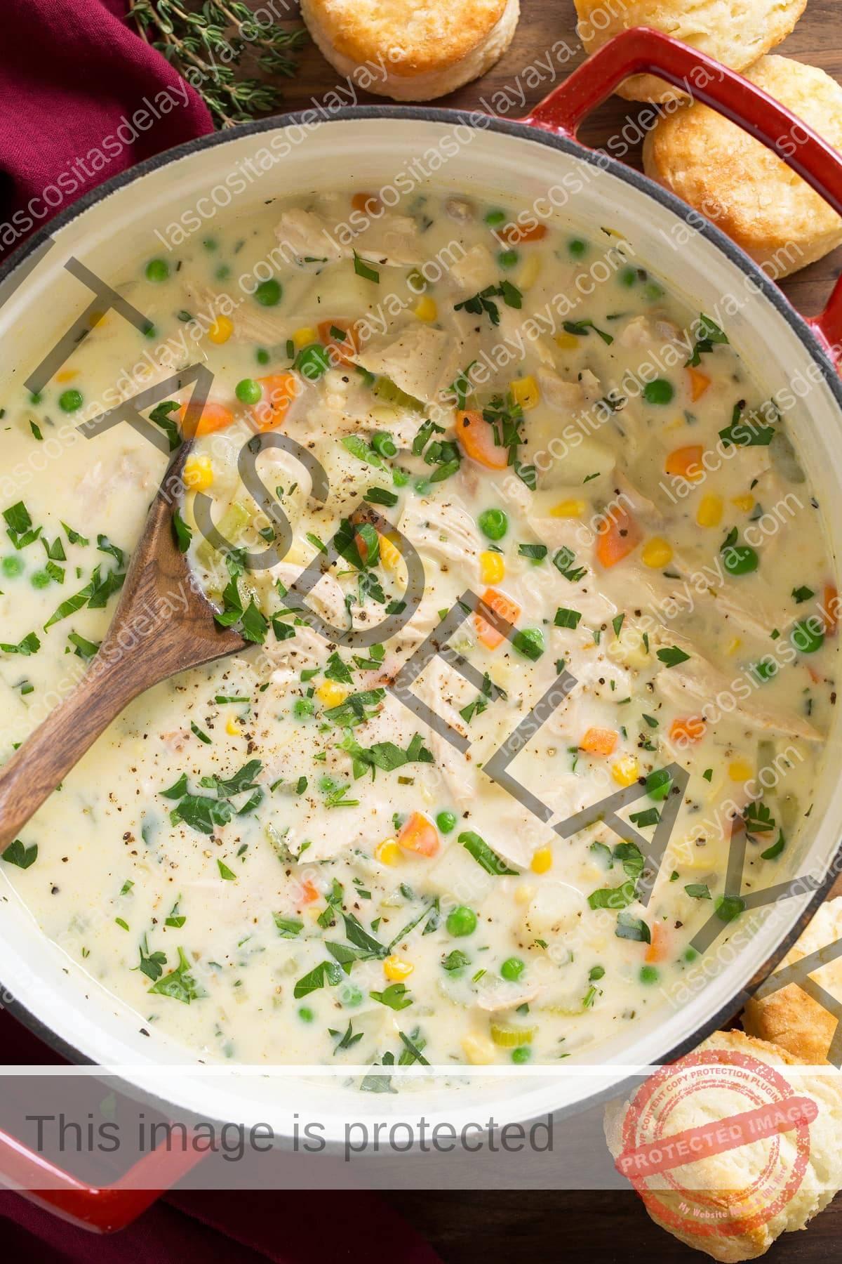 Olla llena de sopa de pastel de pollo con cucharón en la sopa.