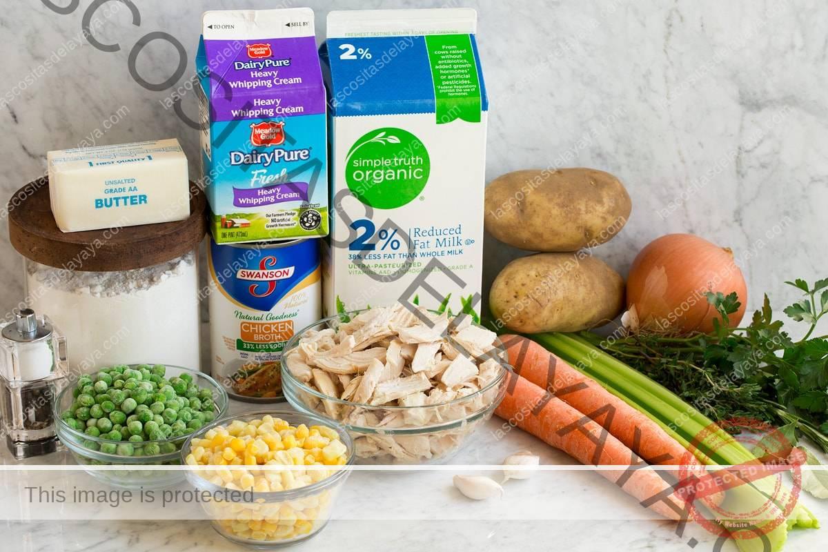 Imagen que muestra los ingredientes necesarios para hacer la sopa de pastel de pollo, que incluyen leche, crema, caldo de pollo, harina, mantequilla, guisantes, maíz, pollo, zanahorias, apio, papas, cebollas, ajo y hierbas frescas.