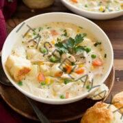 Dos tazones de sopa de pastel de pollo en platos blancos colocados sobre una mesa de madera.  Las galletas se sirven a un lado.