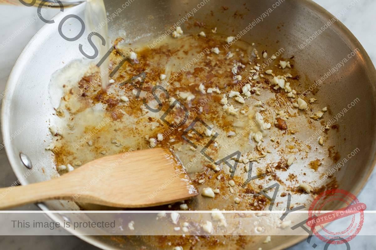 Agregue el caldo de pollo y el limón a los trozos de arroz y dore en el fondo de una sartén.