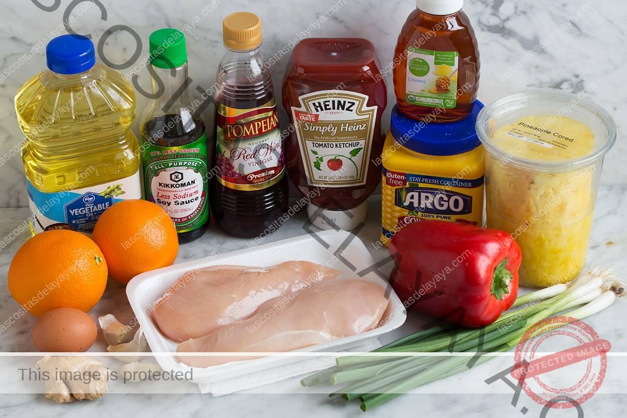 Ingredientes de pollo agridulces que se muestran aquí, que incluyen pechuga de pollo, pimientos, cebollino, ajo, jengibre, naranja, huevo, piña, maicena, miel, vinagre de vino tinto, salsa de soja y aceite vegetal.