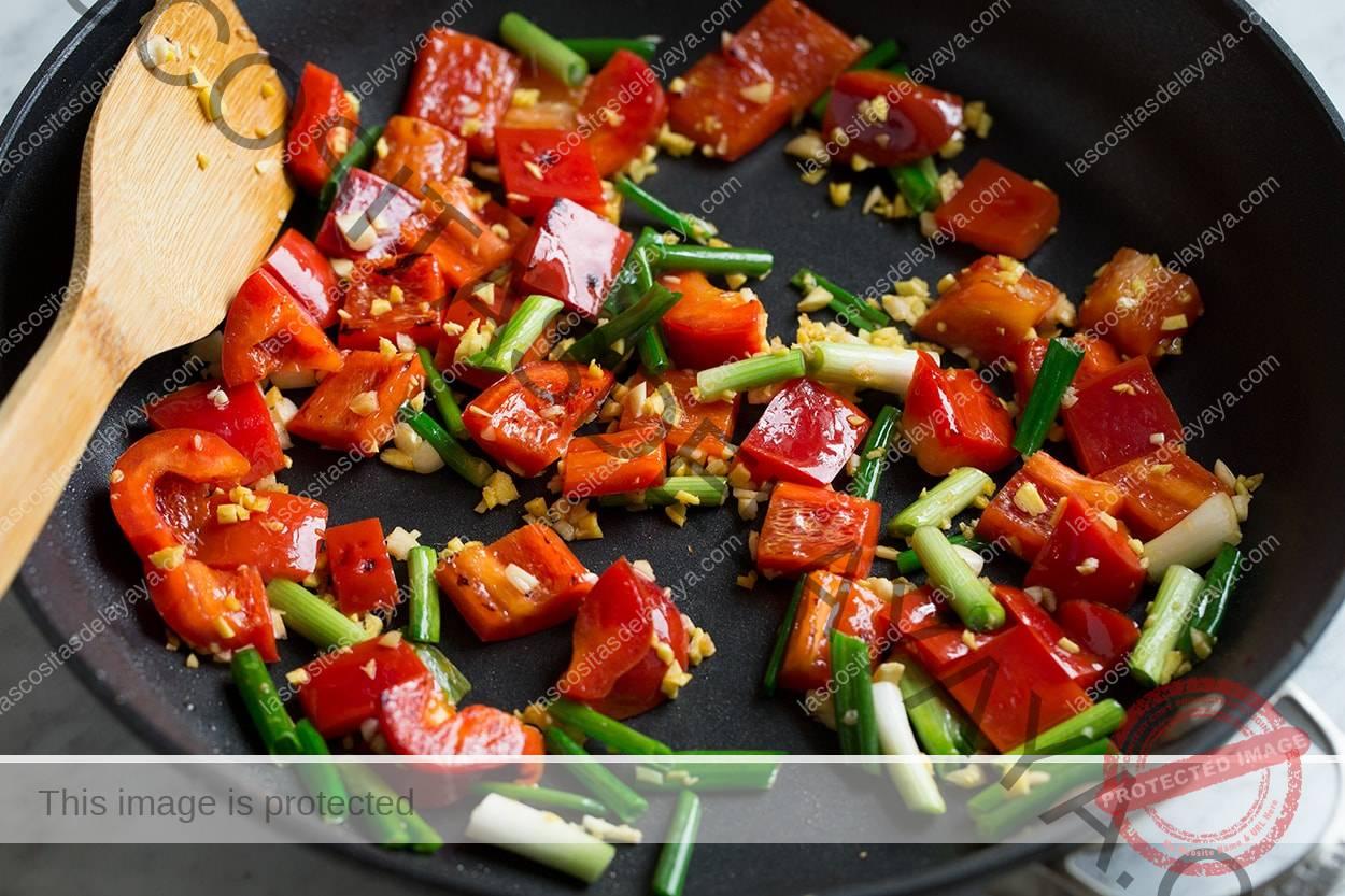 Saltear pimientos, cebollas, ajos y pollo en la sartén