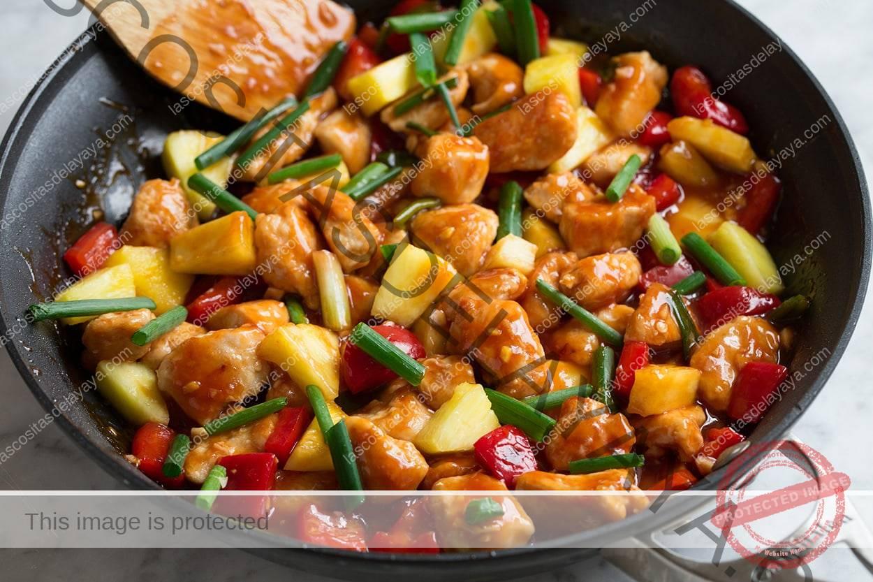 Cocinar salsa con pollo, verduras y piña en la sartén para terminar el pollo agridulce.