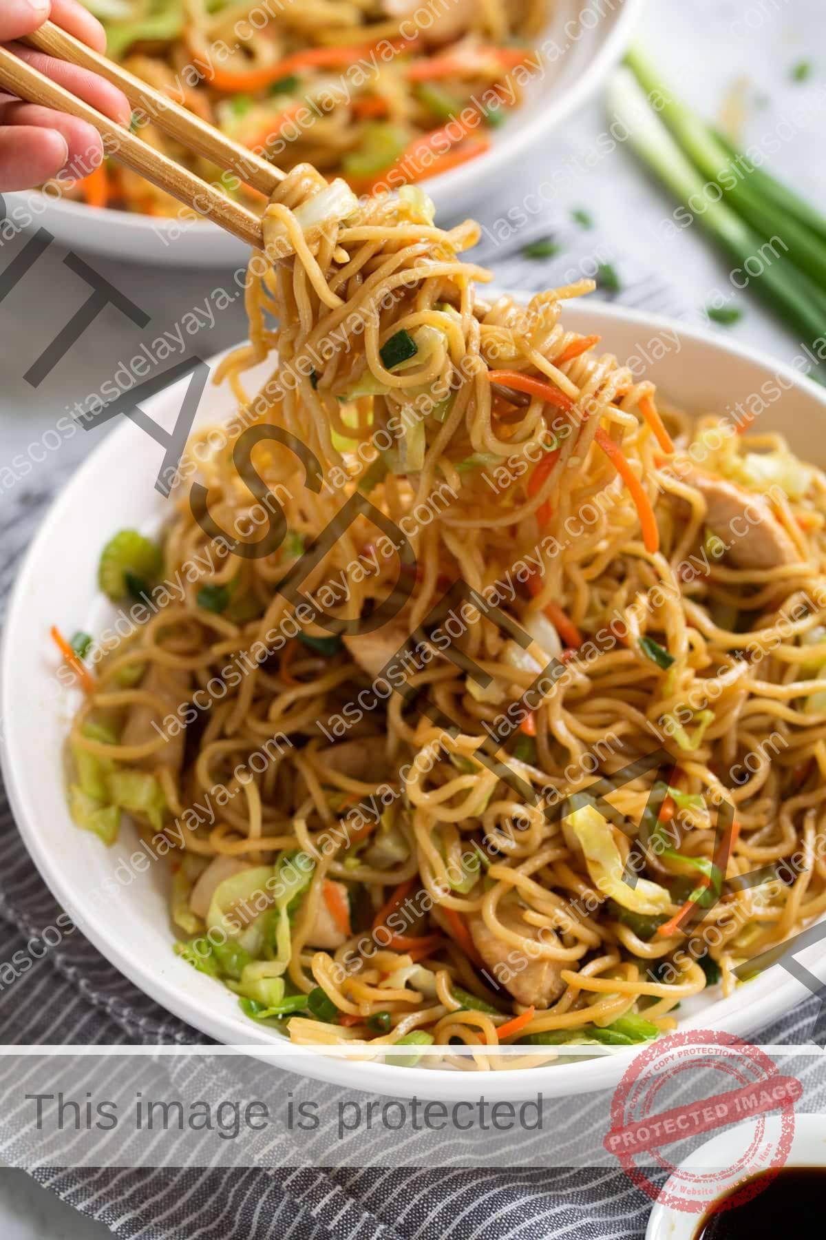Cavando el chow mein con palillos.