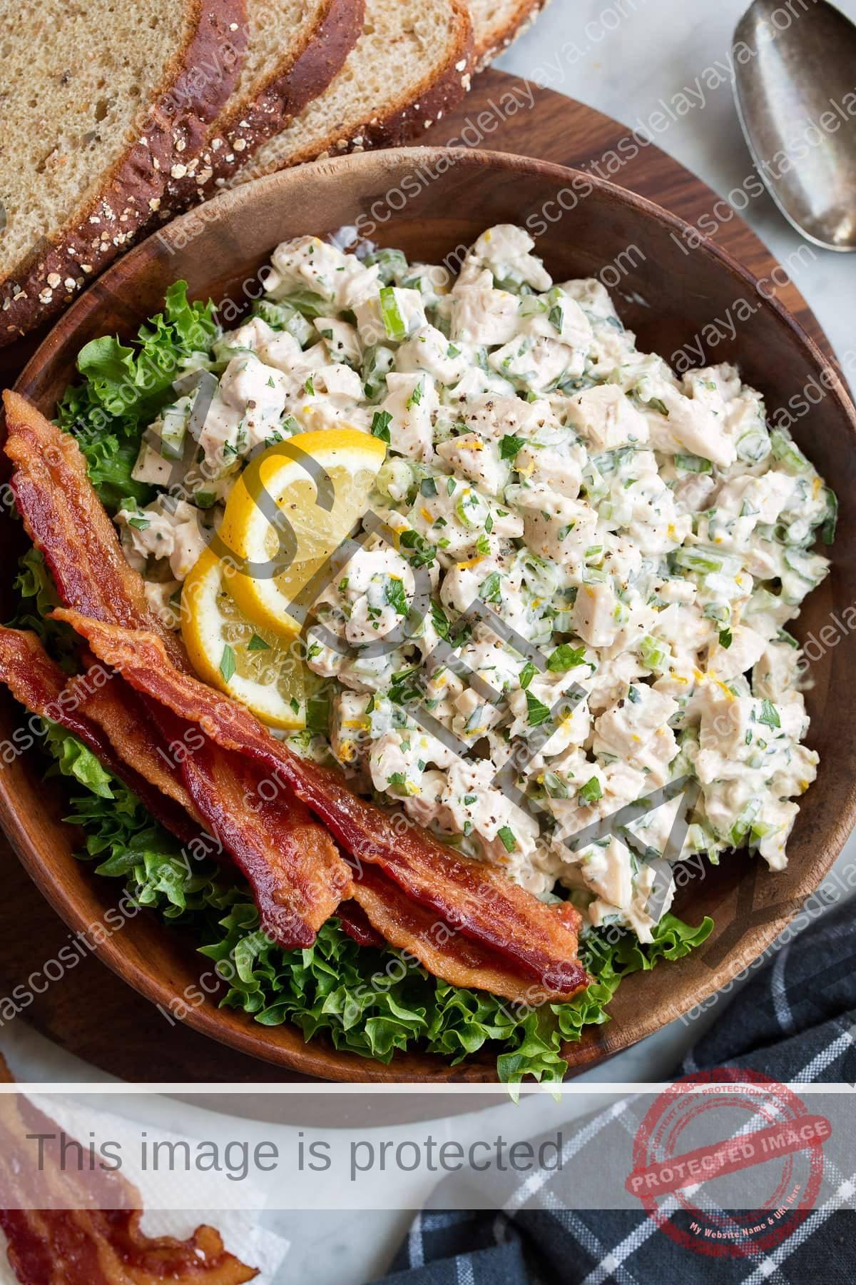 Ensalada de pollo en un cuenco de madera con tocino y lechuga.  Se adorna con rodajas de limón y hay rodajas de pan junto al bol.
