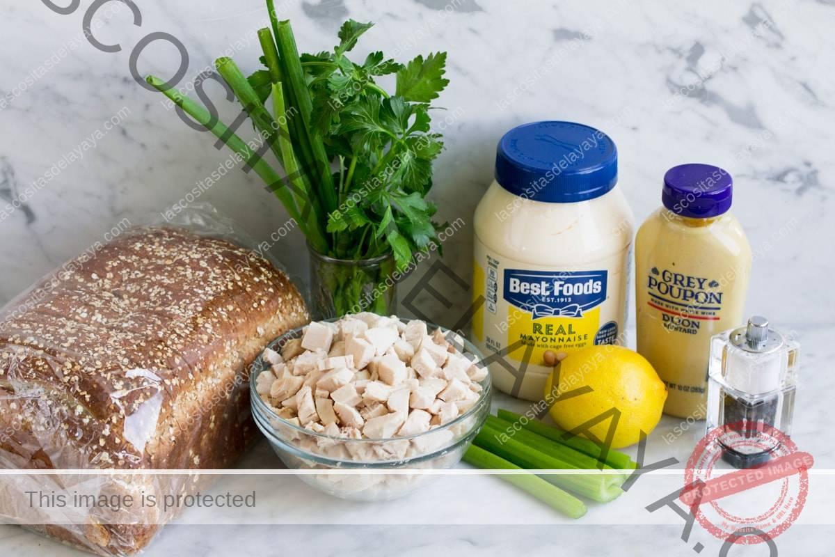 Ingredientes de ensalada de pollo sobre una superficie de mármol, que incluyen trozos de pechuga de pollo cocida, apio, limón, mayonesa, mostaza dijon, perejil, cebollino, sal y pimienta y pan para servir.