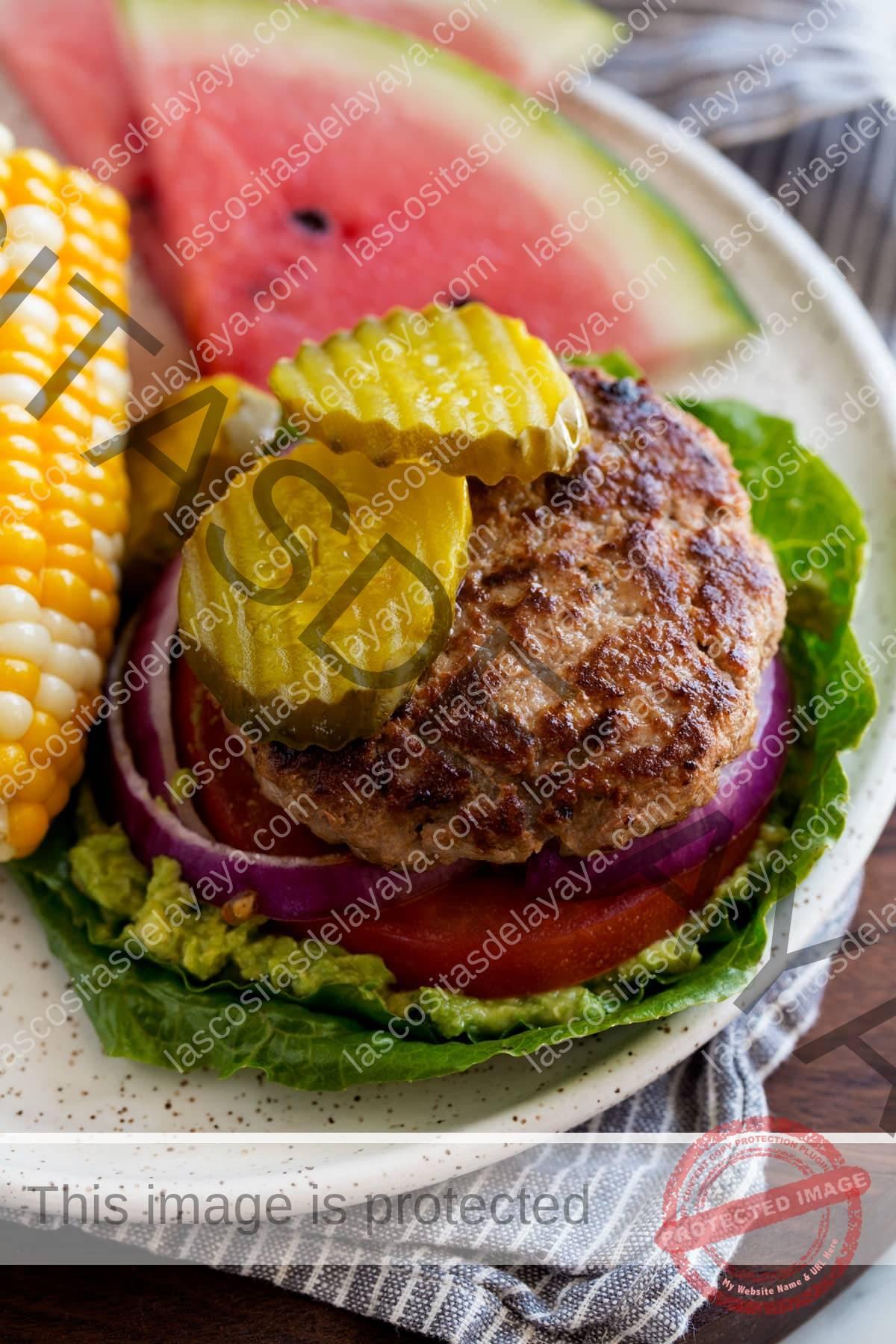 Hamburguesa de pavo baja en carbohidratos y hojas de lechuga.  Servido con maíz y sandía.