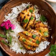 Coxas de frango grelhado de coco tailandês em uma tigela de madeira com arroz e flores decorativas.