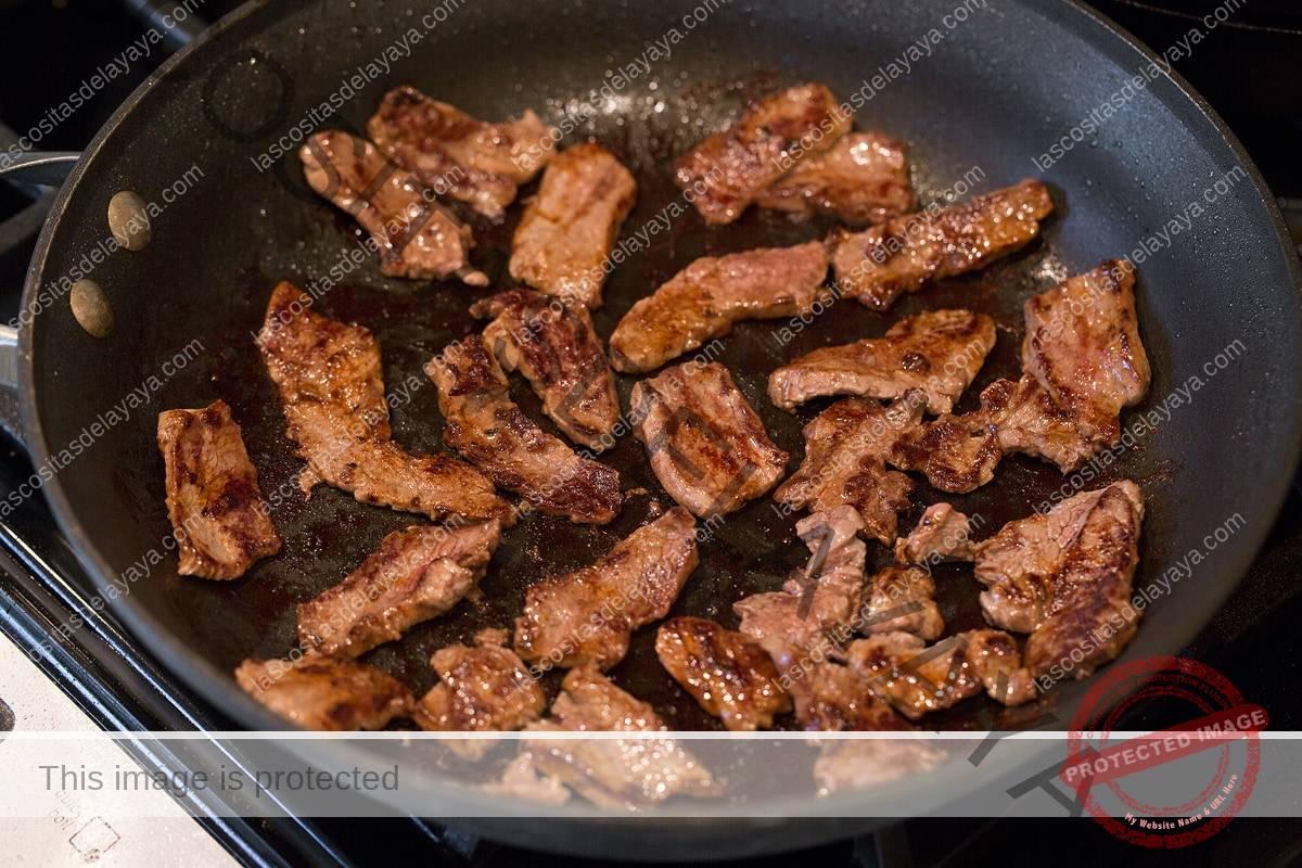 Tiras de filete en rodajas cocinando en una sartén.