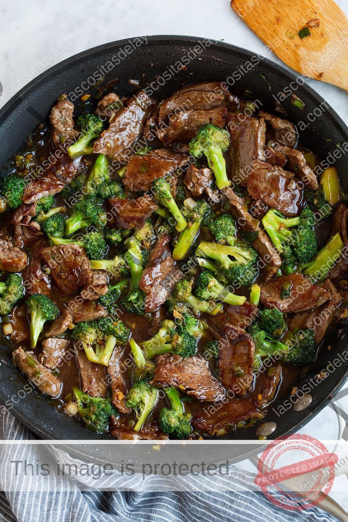 Carne terminada con brócoli con salsa en una sartén.