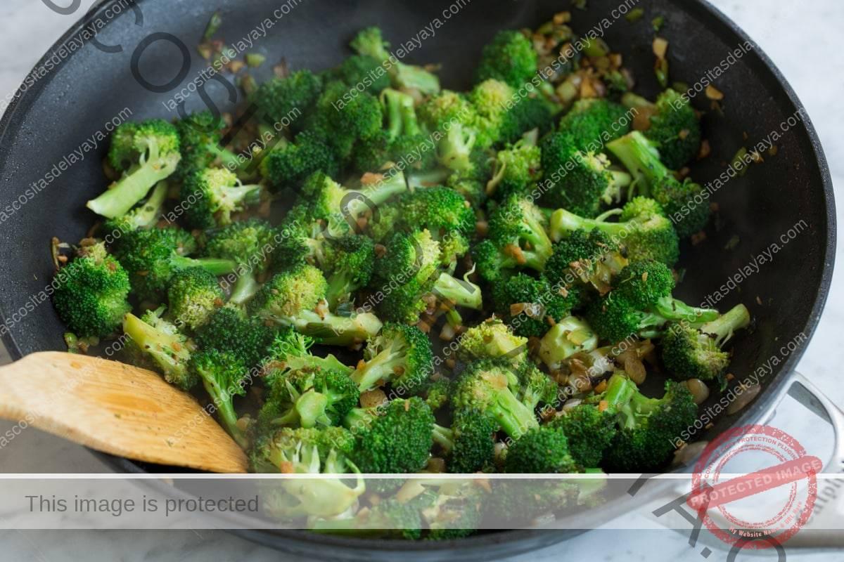 Cocine el brócoli, la cebolla y el ajo en una sartén para hacer carne y brócoli.