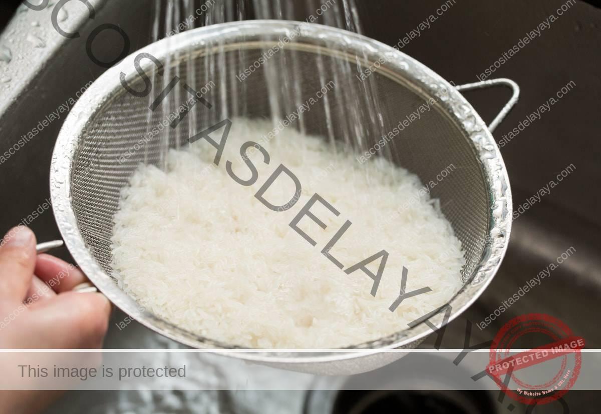Mostrando cómo hacer arroz con coco.  Empezando por enjuagar el aumento con agua en un colador de malla fina.