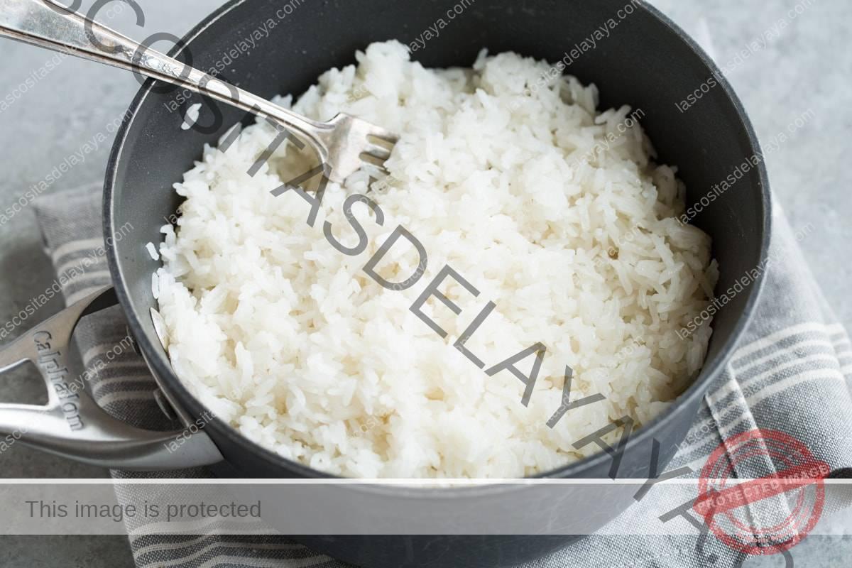 Esponja el arroz de coco terminado en una sartén con un tenedor.