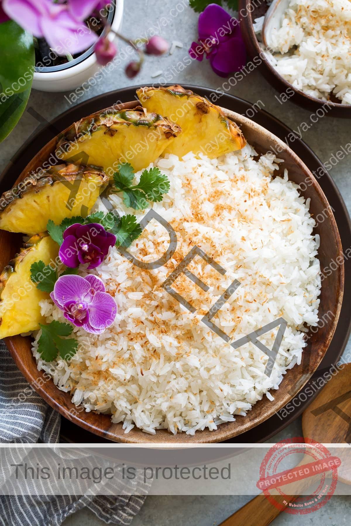 Cuenco de madera relleno de arroz de coco cubierto de flores, cilantro y una guarnición de piña fresca.