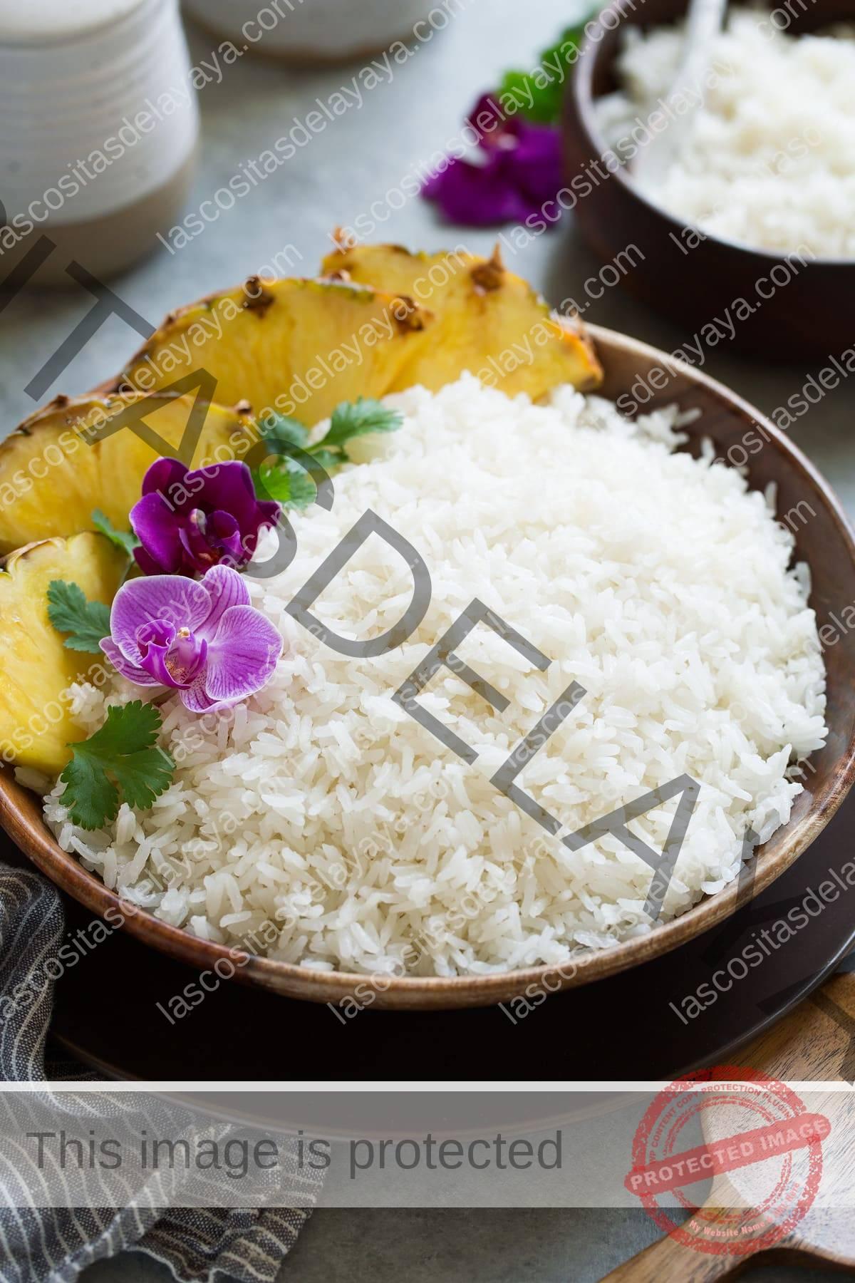 Arroz de coco en un cuenco de madera adornado con orquídeas, cilantro y rodajas de piña al lado.