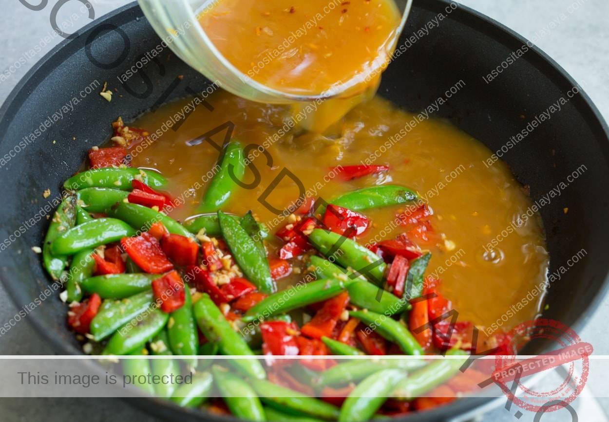Camarones con ajo y naranja agregando salsa de naranja frita a la sartén con las verduras