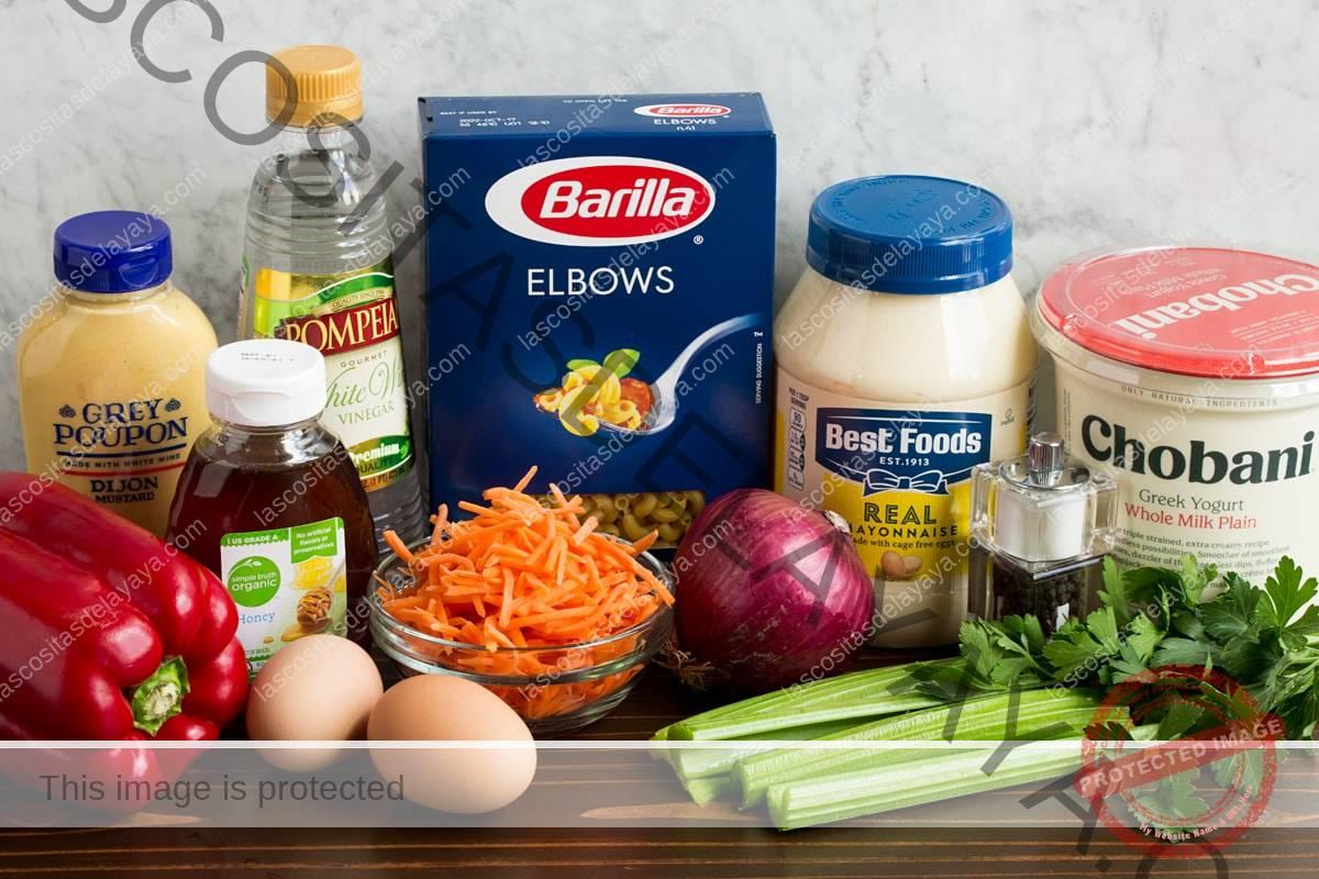 Aquí se muestran los ingredientes de la ensalada de pasta.  Incluye mayonesa, yogur griego, mostaza dijon, miel, huevos, zanahorias, pimientos, apio, perejil, vinagre, sal y pimienta.