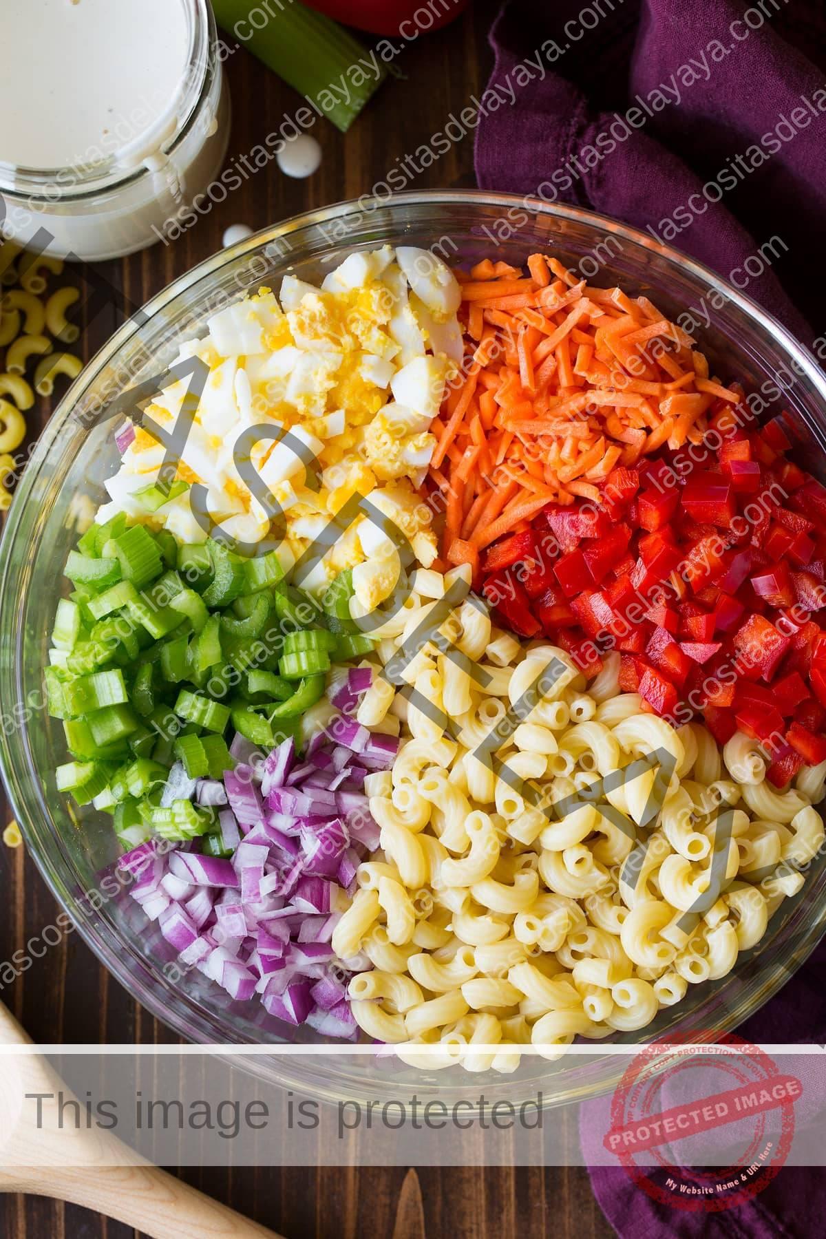Ingredientes de la ensalada de pasta en un recipiente de vidrio antes de mezclar.