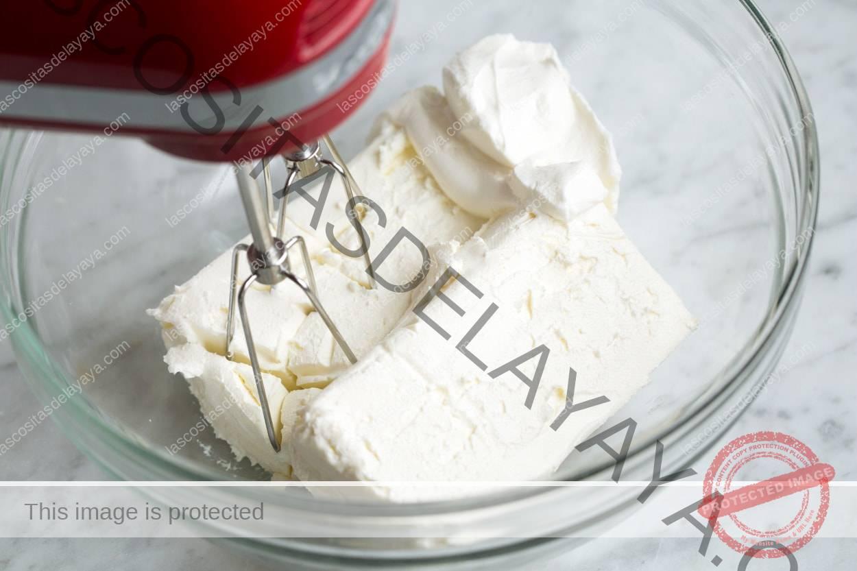 Mostrando cómo hacer una bola de queso.  Mezcle la crema de queso crema y las especias en un bol con una batidora eléctrica.