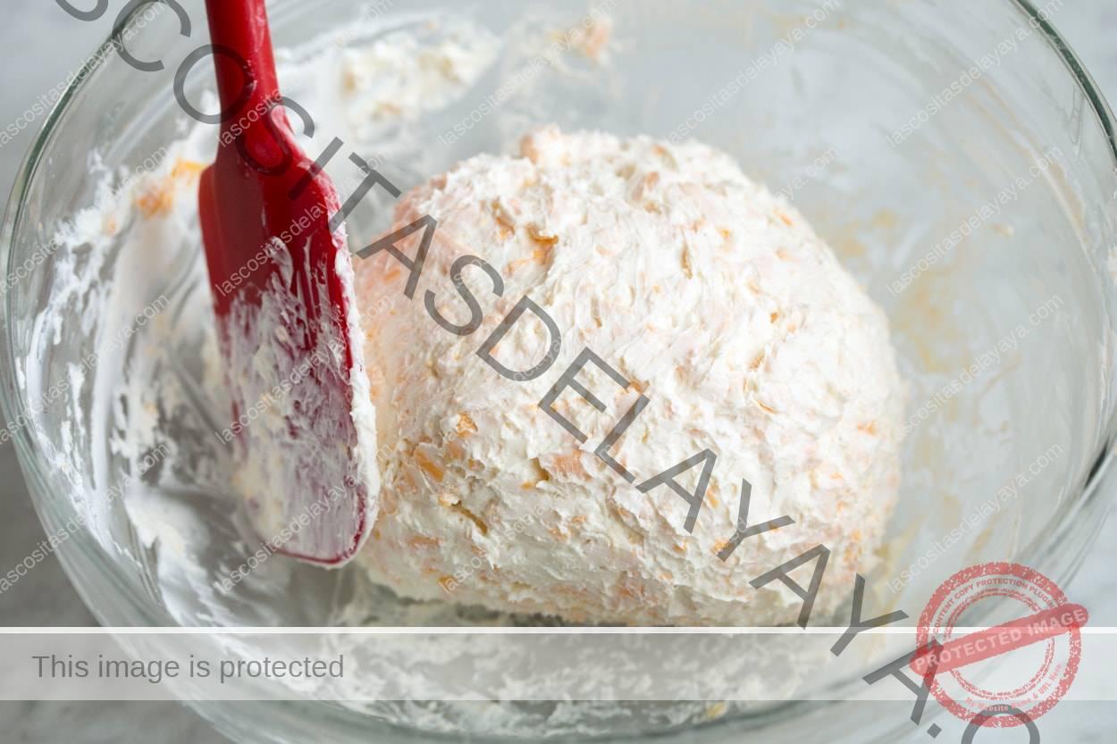 Con una espátula, forme una bola de queso fría en un tazón.