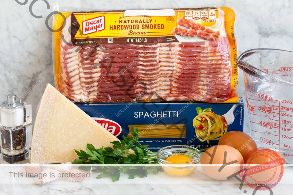 Imagen de los ingredientes de la pasta carbonara.  Incluye espaguetis, tocino, perejil, parmesano, huevos, yema de huevo, agua, ajo, sal y pimienta.