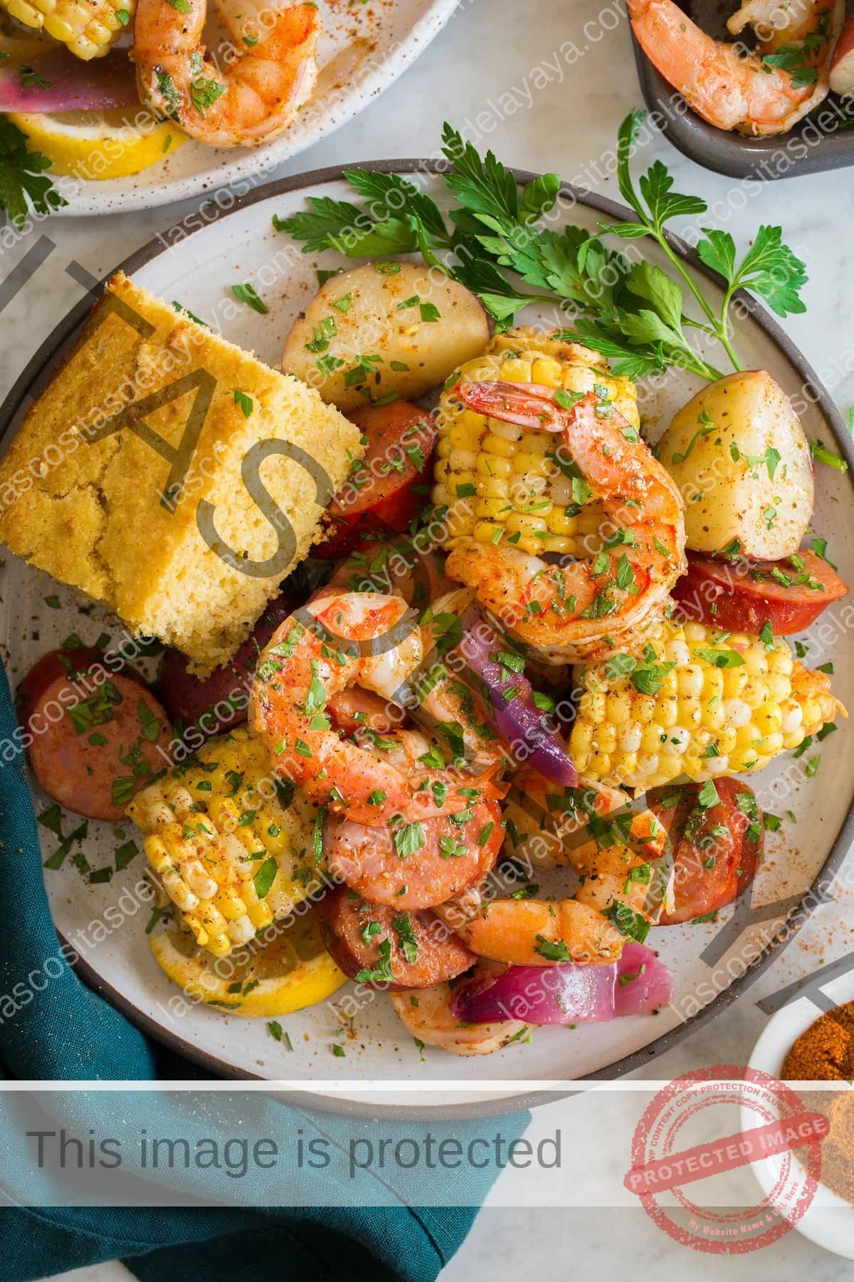 Imagen que muestra una porción de camarones hirviendo en un plato blanco con un toque de porción de pan de maíz.