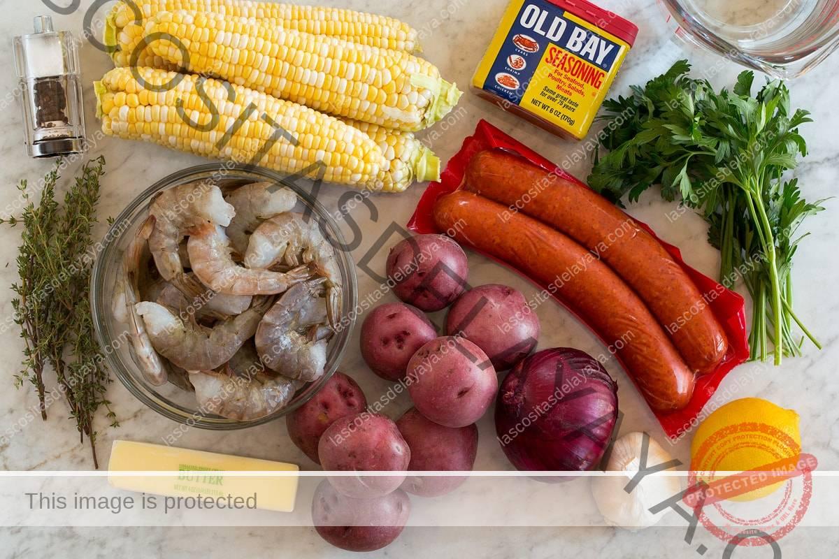 Imagen de los ingredientes utilizados para hervir los camarones.  Incluye camarones, mazorcas de maíz, salchicha andouille, papas rojas, cebollas, mantequilla, limón, perejil, tomillo, ajo, sal y pimienta y agua.