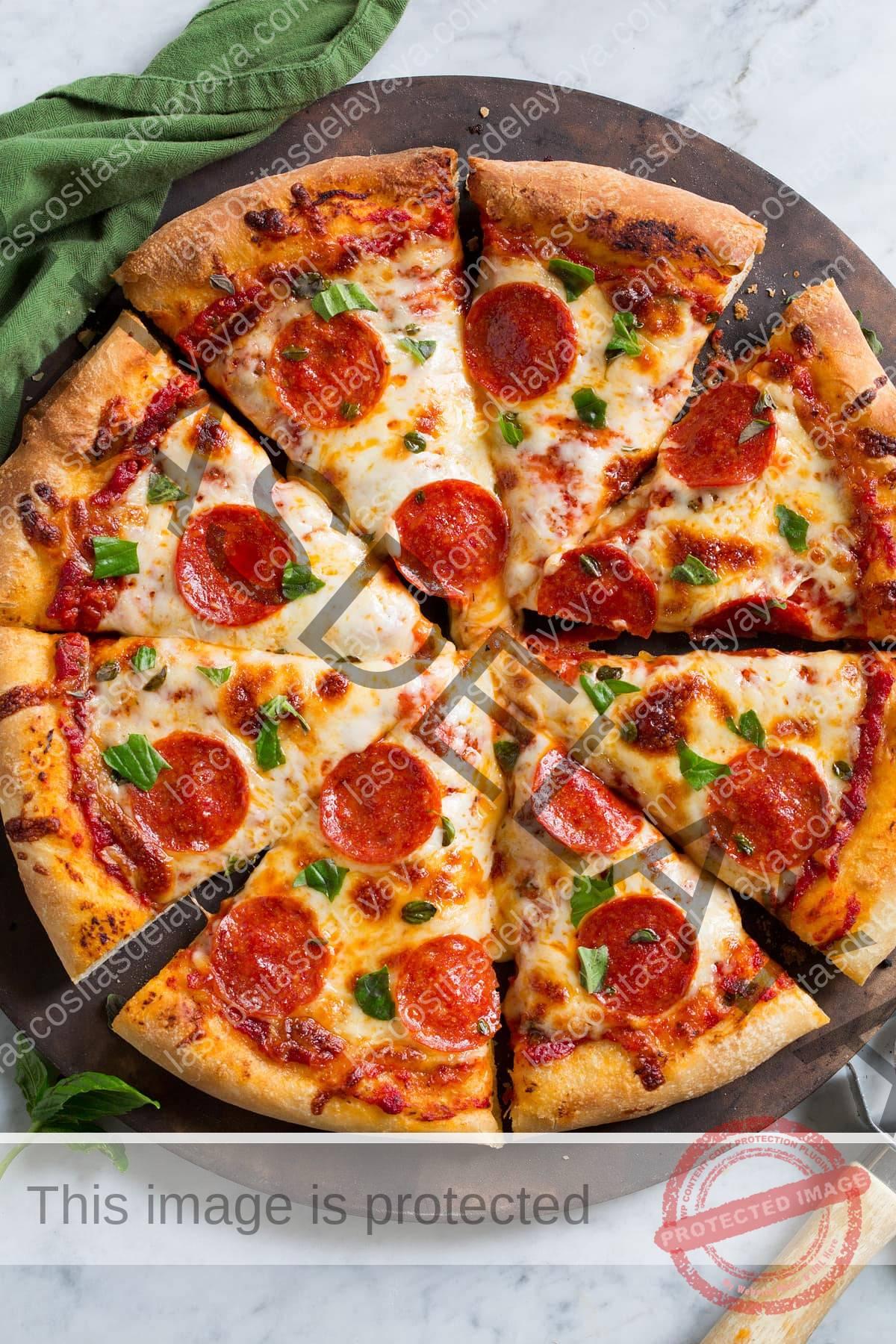 Imagem aérea de pizza de pepperoni com crosta caseira. A pizza é cortada em 8 fatias.