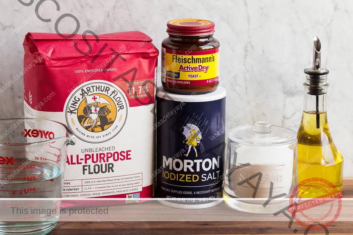 Imagem dos ingredientes usados para fazer massa de pizza. Inclui farinha de trigo, água, sal, fermento, açúcar e azeite.