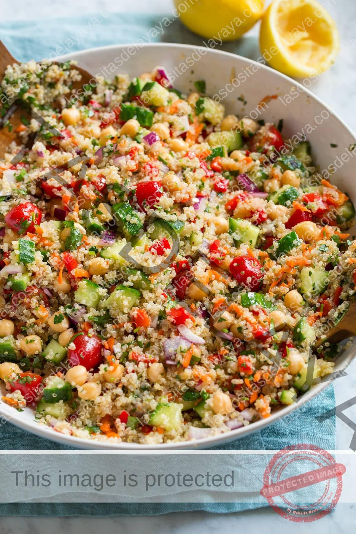 Ensalada de quinua saludable en un bol.  Ensalada muestra quinua, pepino, tomate, zanahoria, cebolla morada, garbanzos y hierbas.