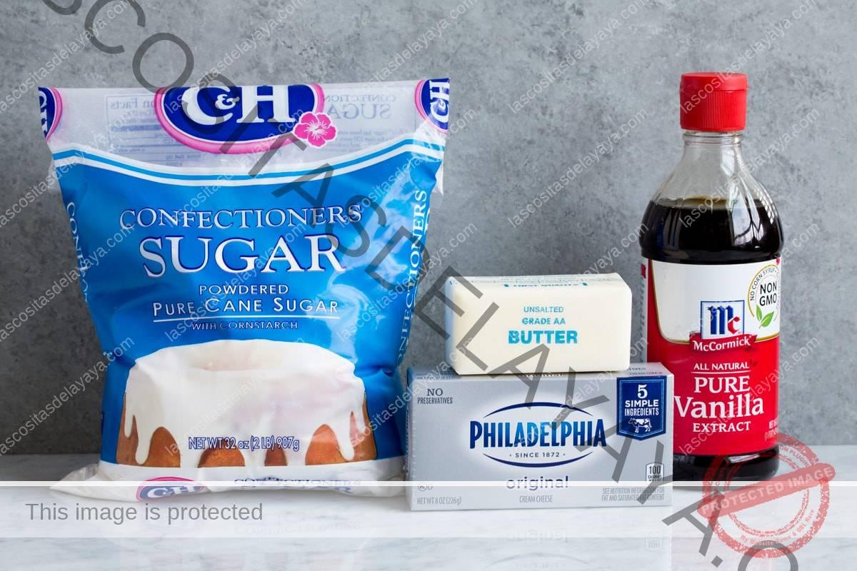 Los ingredientes utilizados para hacer glaseado de queso crema que se muestran aquí, incluyen azúcar en polvo, queso crema, mantequilla y extracto de vainilla.