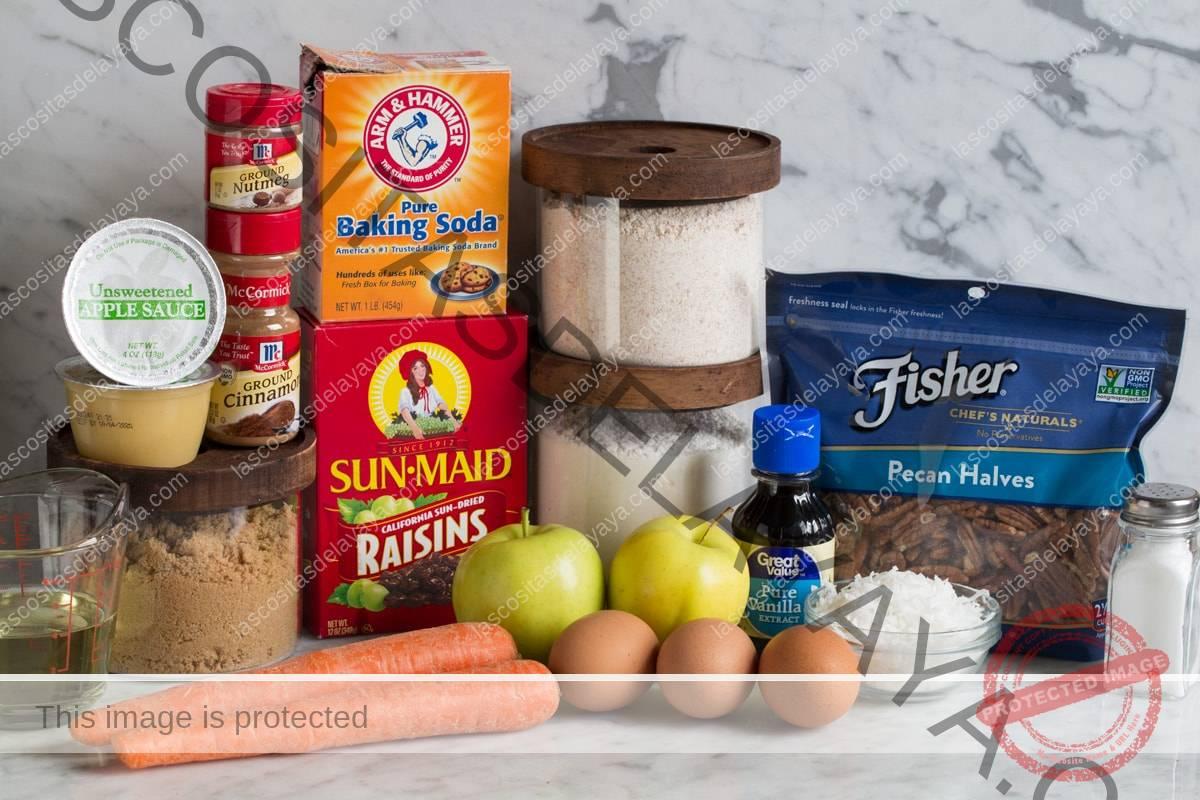 Los ingredientes necesarios para los muffins de gloria de la mañana que se muestran aquí, incluida la harina de trigo, harina blanca, bicarbonato de sodio, canela, nuez moscada, sal, azúcar morena, manzanas, zanahorias, pasas, coco, huevos, aceite vegetal, vainilla, nueces y mermelada de manzana.