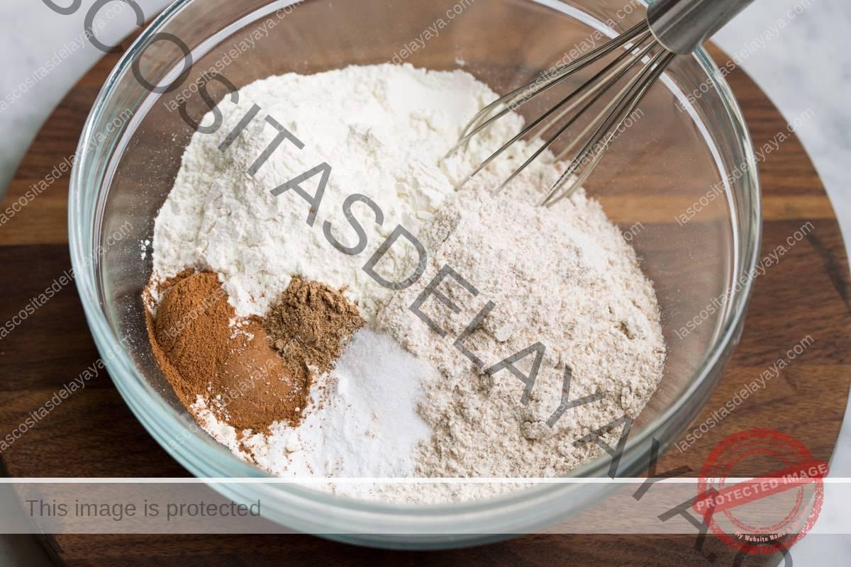 Mostrando cómo hacer muffins de campanilla.  Batir la harina blanca, la harina de trigo, la canela, la nuez moscada, el bicarbonato de sodio y la sal en un bol de vidrio.