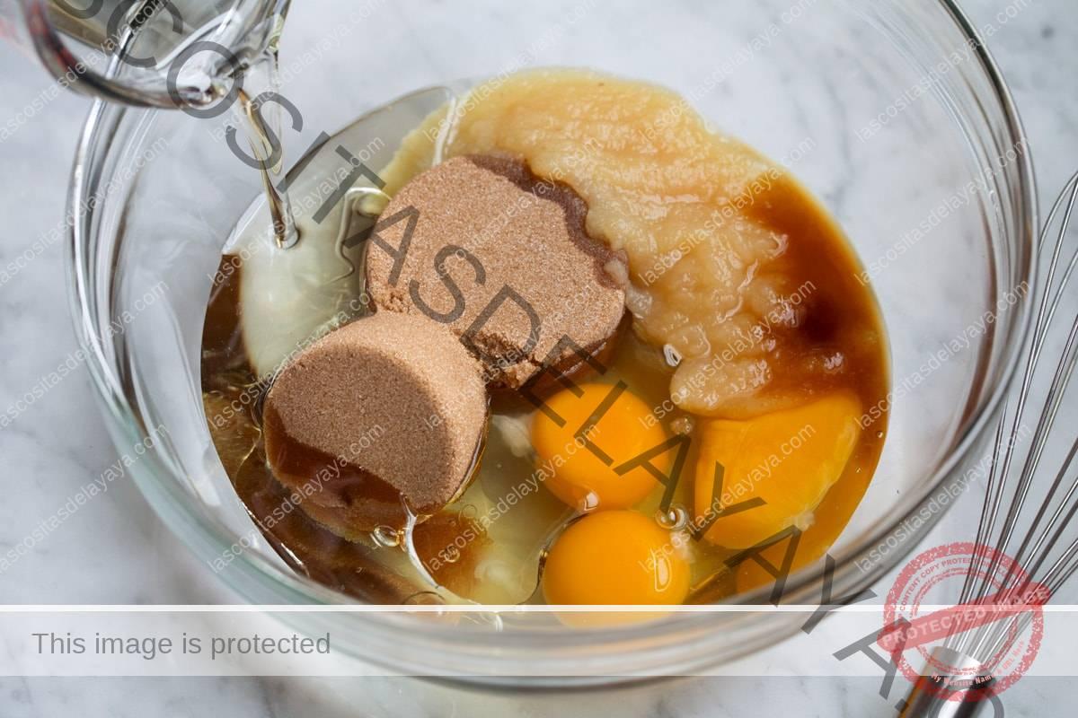 Mostrando cómo hacer muffins de gloria de la mañana.  Mezcle los huevos, el aceite, el puré de manzana, el azúcar morena y la vainilla en un bol de vidrio.