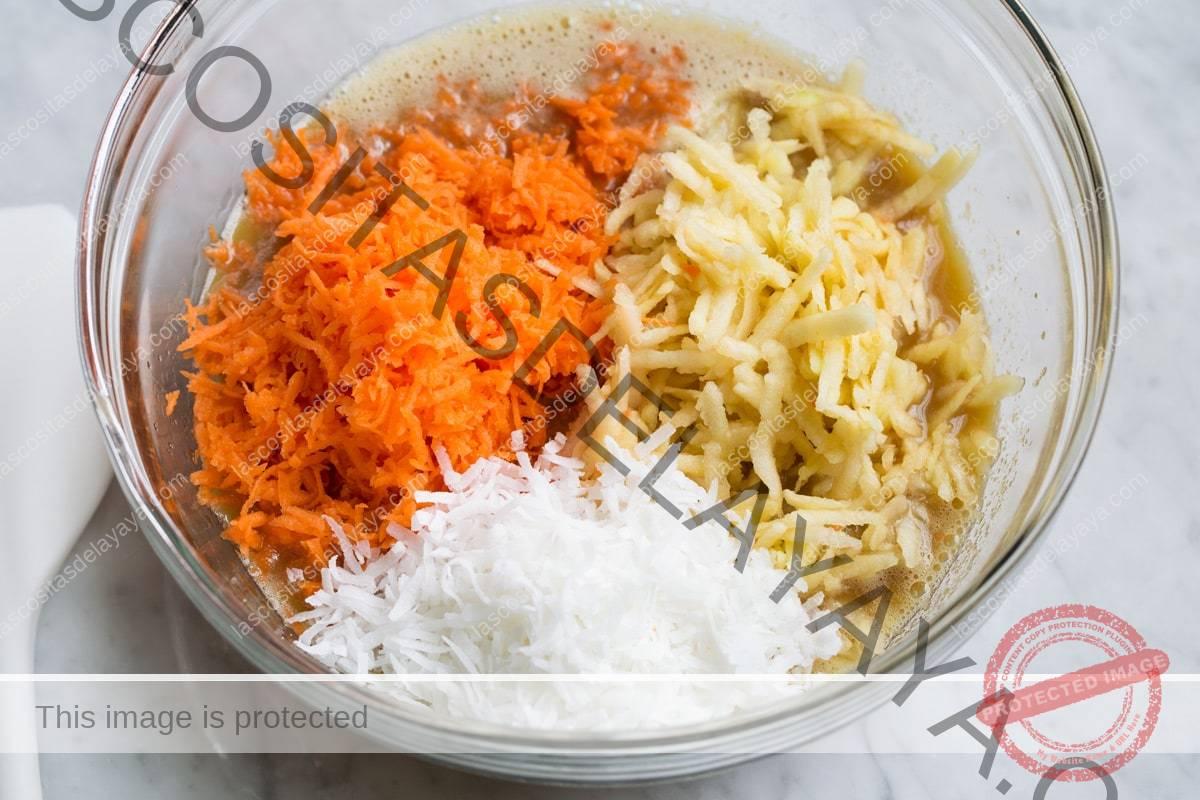 Agregue zanahoria rallada, manzana y coco a la masa para muffins de gloria de la mañana en el tazón de vidrio.