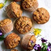 Imagen aérea de muffins de gloria de la mañana sobre una superficie de mármol decorada con flores de primavera.