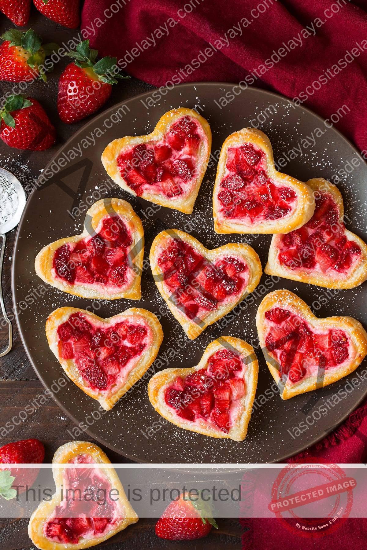 Tortas de desayuno cortadas en forma de corazón, cubiertas con queso crema y fresas endulzadas.