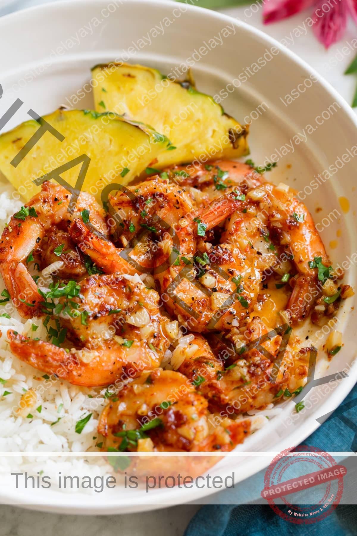 Cerrar imagen de camarones al ajillo hawaianos servidos sobre arroz blanco con rodajas de piña fresca.