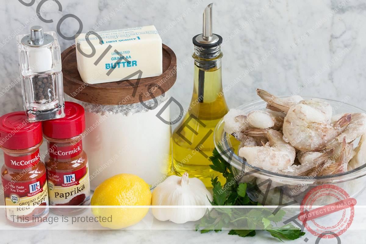 Imagen de los ingredientes utilizados para hacer camarones con ajo hawaiano.  Incluye camarones crudos, aceite de oliva, perejil, ajo, limón, harina, mantequilla, pimentón, pimienta de cayena, sal y pimienta.