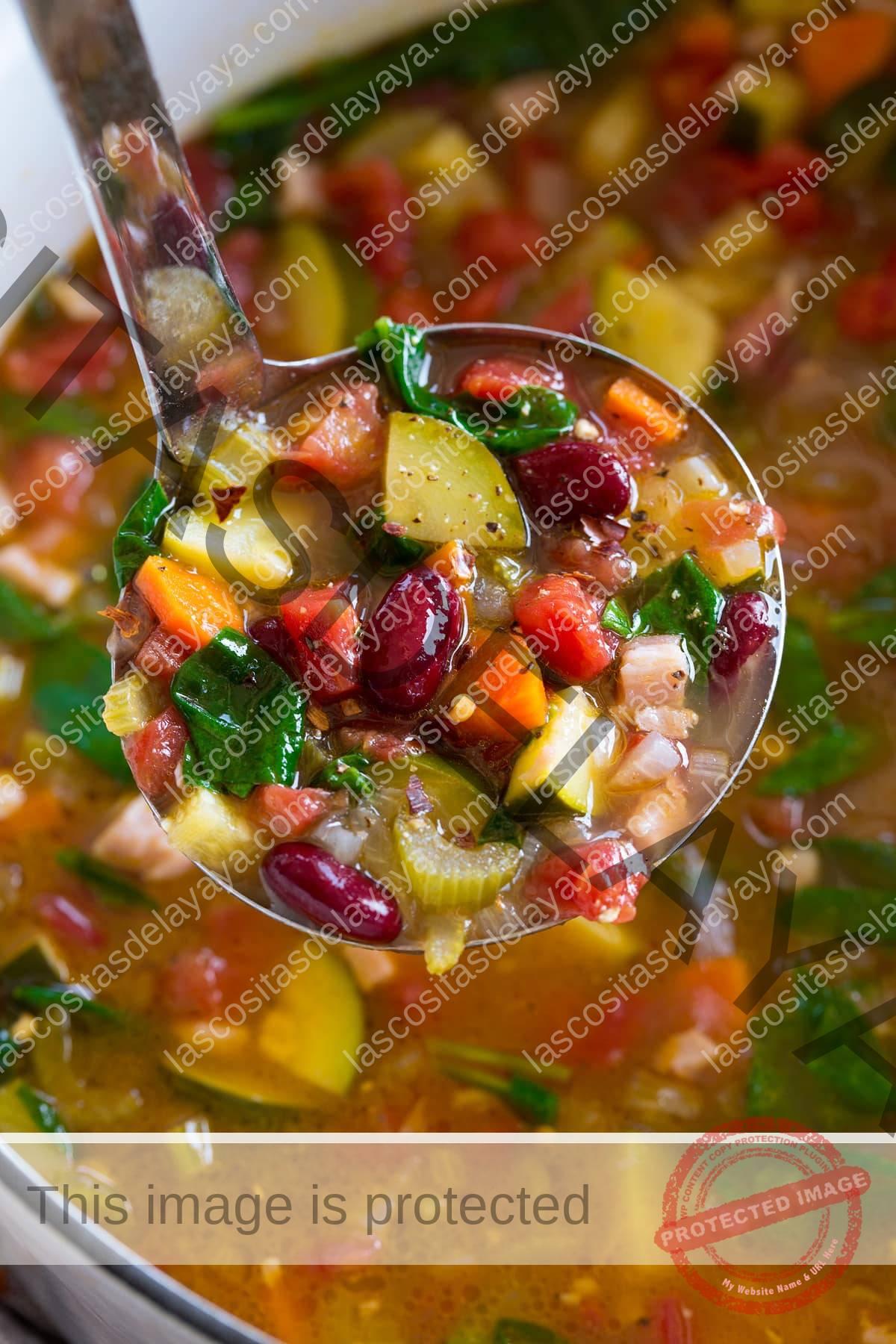 Cerrar imagen de un cucharón lleno de sopa minestrone.