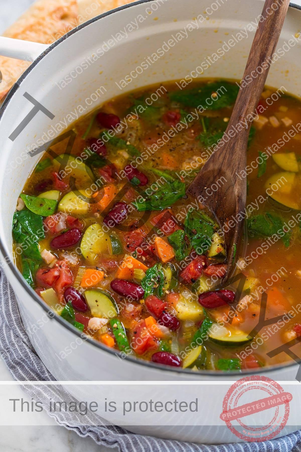 Olla llena de sopa minestrone que se muestra en el lateral.