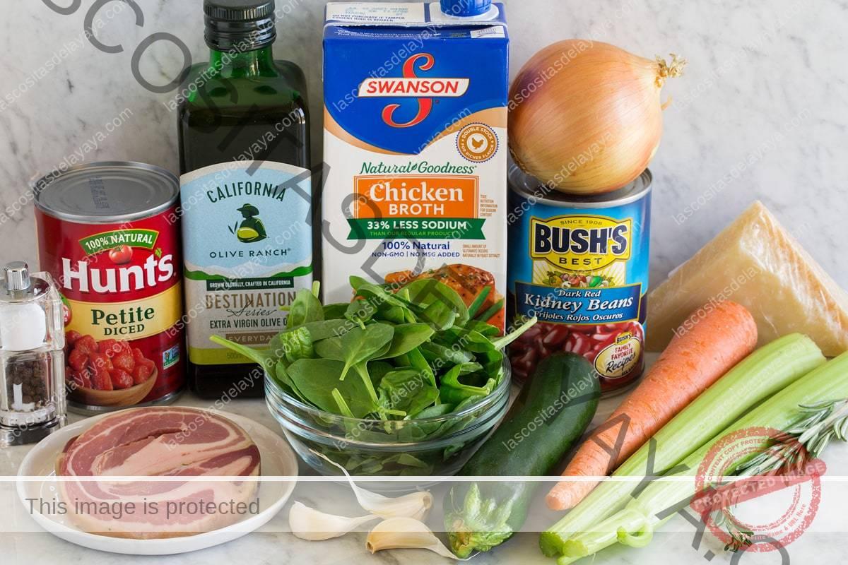 Imagen de los ingredientes utilizados para hacer la sopa Minestrone.  Muestra apio, zanahoria, romero, calabacín, parmesano, frijoles, cebolla amarilla, espinacas, caldo de pollo, ajo, panceta, aceite de oliva, tomates enlatados, sal y pimienta.