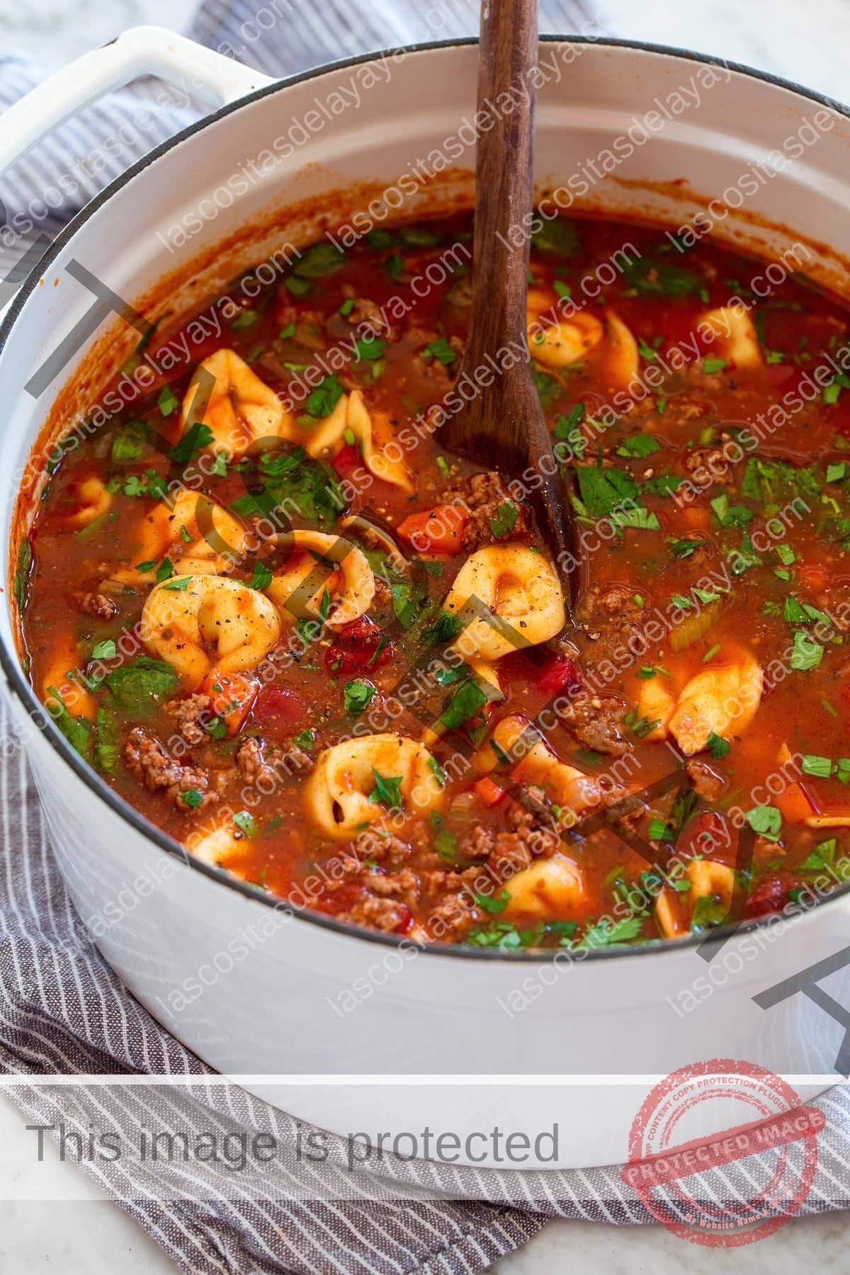 Cacerola blanca llena de sopa de tortellini.