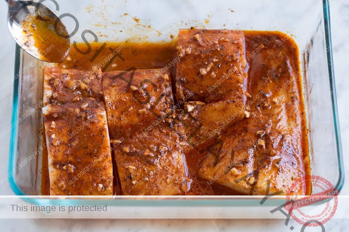Colher a marinada sobre o peixe na assadeira.