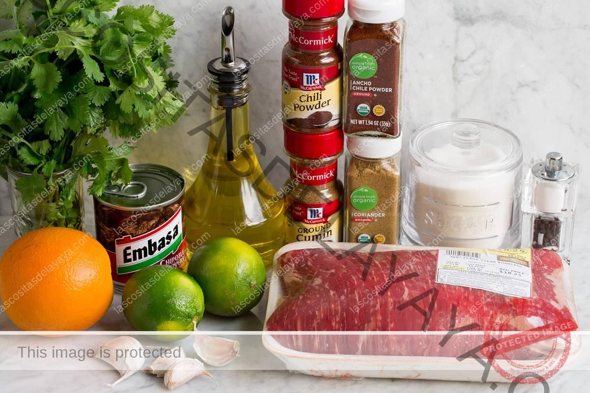 Imagen de los ingredientes utilizados para hacer carnes asadas y adobadas.  Incluye bife, cilantro, aceite de oliva, chile en polvo, comino, chile chipotle, limón, naranja, azúcar, ajo, sal y pimienta.