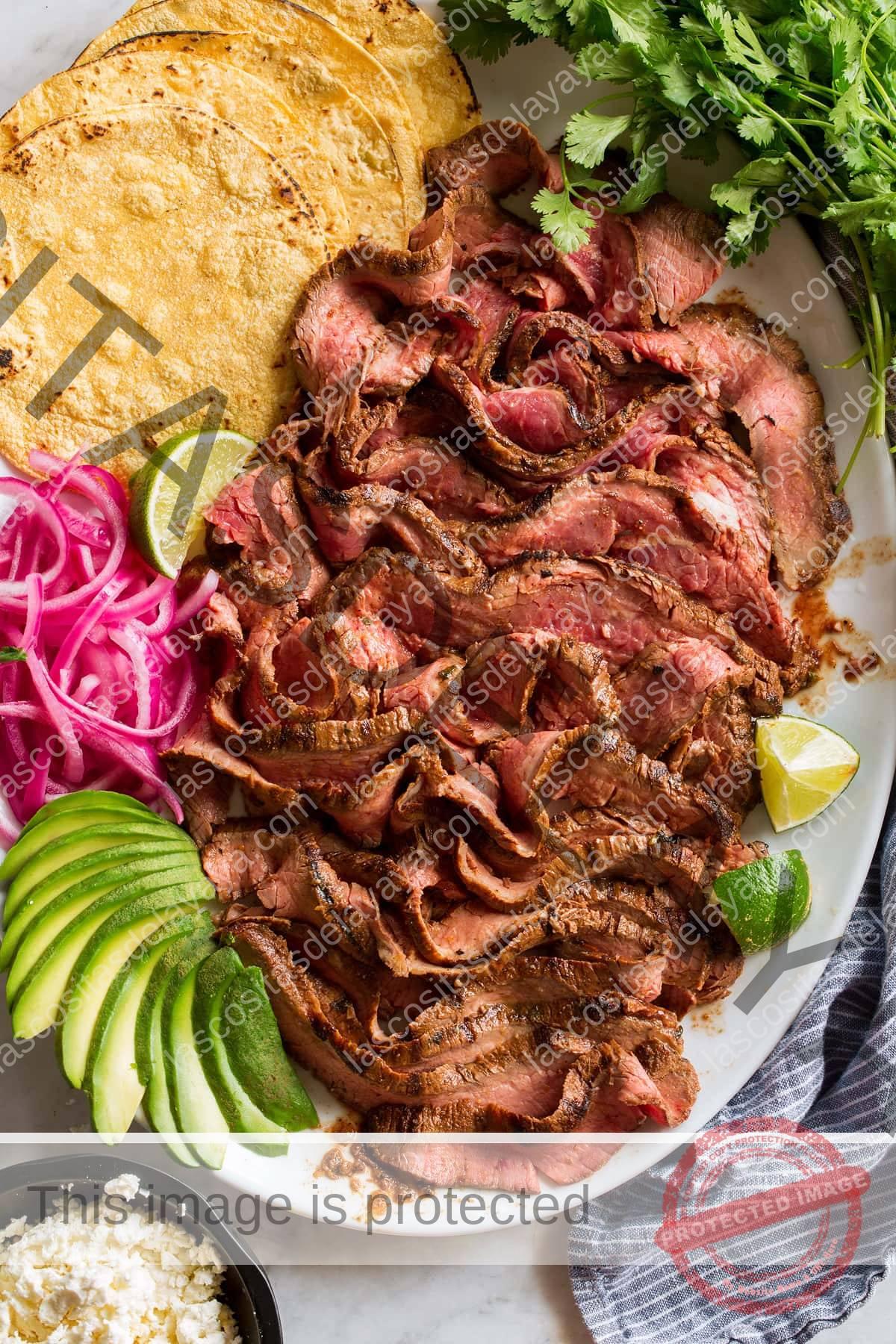 Imagen aérea de asada de carne en rodajas finas en una fuente con tortillas, cebolla, aguacate, limón y cilantro.