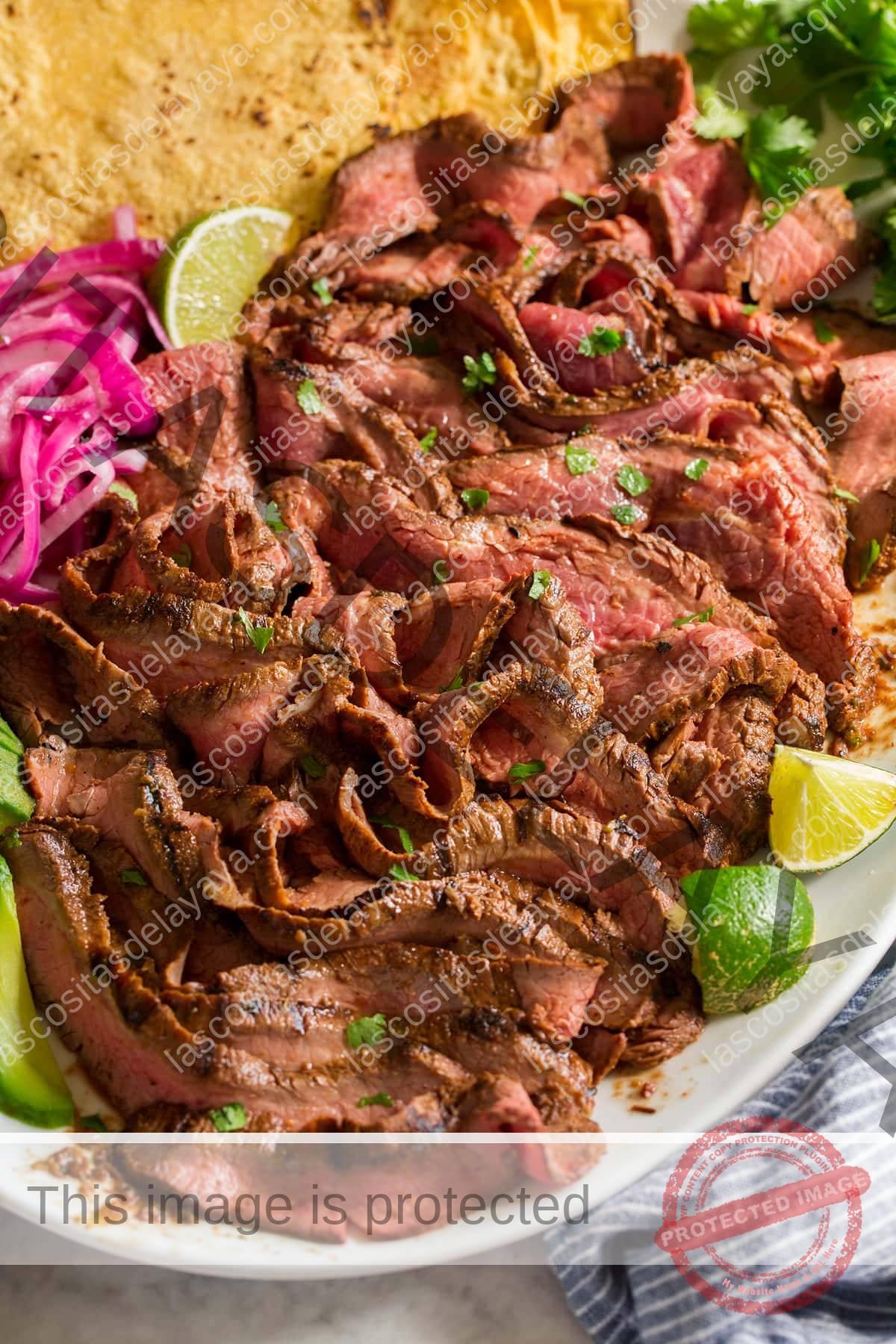 Tiras de carne asada en rodajas que se muestran en un plato blanco desde una vista lateral.